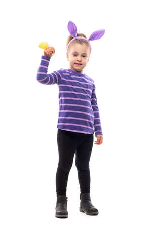 Cute young girl with pink bunny ears hat waving at camera with Eater yellow egg. Full body isolated on white background