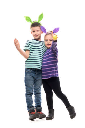 Happy kids boy and girl posing with easter eggs and bunny ears. Full body isolated on white background