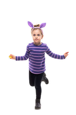 Cute uncertain young girl with bunny ears balancing and standing on one leg. Full body isolated on white background