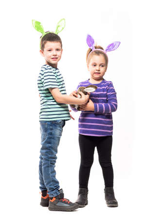 Playful young children with bunny ears hat playing with Easter rabbit toy. Full body isolated on white background