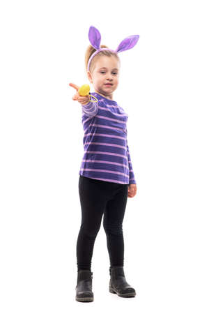 Caring young cute girl with bunny ears sharing and giving Easter egg at camera. Full body isolated on white background