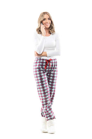 Happy relaxed woman beauty at home in sleepwear talking on the phone smiling at camera. Full body length isolated on white background. Stockfoto