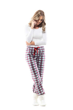 Feminine beauty woman in casual cozy home wear clothes on the phone looking down and smile. Full body length isolated on white background. Stockfoto