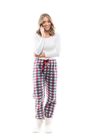 Young beautiful woman in pajamas and knitted socks relaxing and smiling on the phone. Full body length isolated on white background.