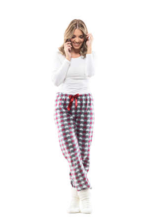 Cheerful laughing beautiful young woman in pajamas talking on phone having fun. Full body length isolated on white background.