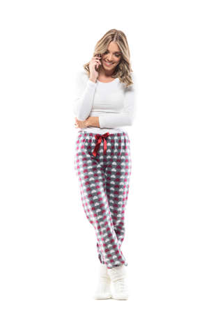 Beautiful smiling young woman talking on the phone looking down wearing comfy nightwear. Full body length isolated on white background.