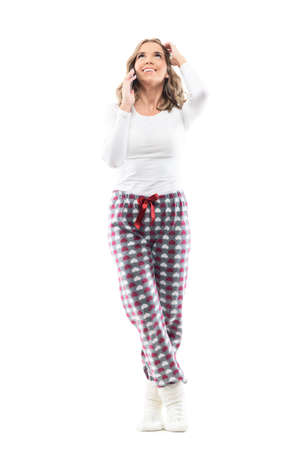 Carefree candid young pretty woman in pajamas looking up talking on the phone and touch hair. Full body length isolated on white background. Stockfoto