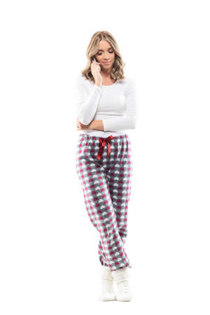 Candid relaxed young woman in comfy home clothes speaking on the phone looking down. Full body length isolated on white background.