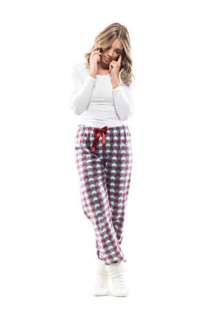 Pensive thoughtful serious young woman in home wear pajama talking on the phone looking down. Full body length isolated on white background.
