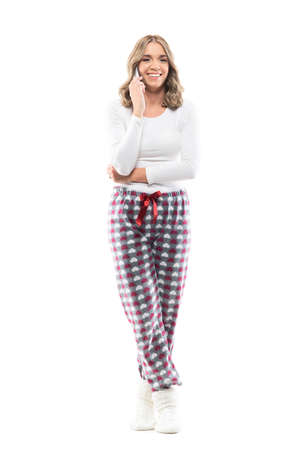 Cute young pretty woman laughing and having fun while talking on the cell phone in pajama. Full body length isolated on white background. Stockfoto