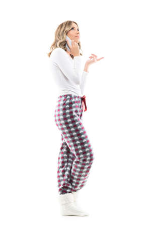 Confused young pretty woman in pajamas talking on the cell phone looking up pointing finger puzzled. Full body length isolated on white background.