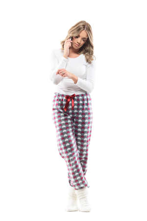 Young pretty woman on the phone waiting and checking time in home wear pajama. Full body length isolated on white background. Stockfoto