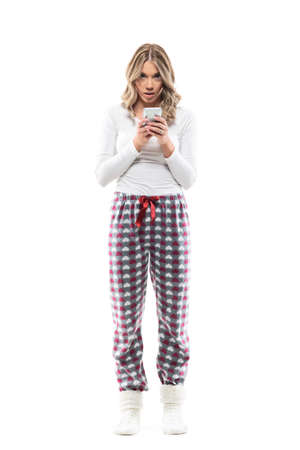 Shocked fascinated young woman using smart phone looking at camera in cozy home clothes. Full body length isolated on white background. Stockfoto