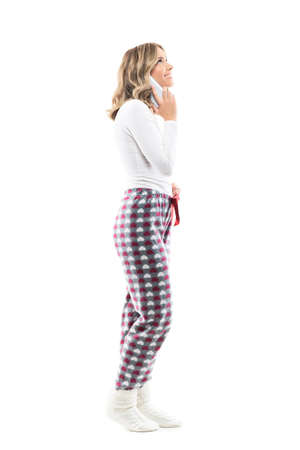 Side view of happy beautiful young woman in pajamas talking on the phone looking up. Full body length isolated on white background.