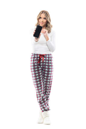 Cute young woman at home in cozy pajamas showing and advertising cellphone blank screen. Full body length isolated on white background.