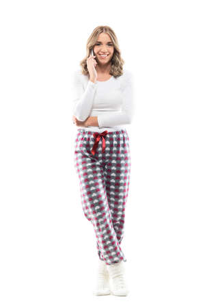 Happy young pretty woman in cozy pajama talking on the cell phone smiling at camera. Full body length isolated on white background.