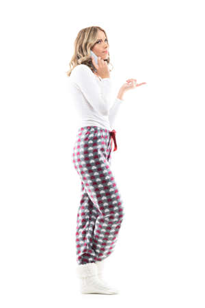 Side view of confused and displeased young woman in pajamas talking on the phone pointing finger. Full body length isolated on white background. Stockfoto