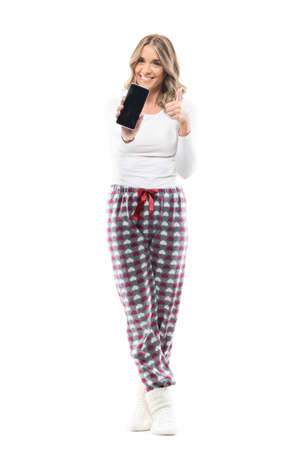 Cheerful excited young woman in home wear clothes showing blank smart phone screen at camera. Full body length isolated on white background. Stockfoto