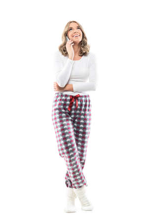Happy pretty young woman in comfy pajama talking on the phone looking up and smile. Full body length isolated on white background. Stockfoto