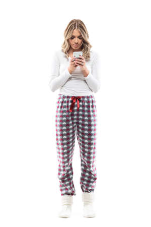 Busy serious young woman in pajamas using phone browsing internet. Full body length isolated on white background. Stockfoto