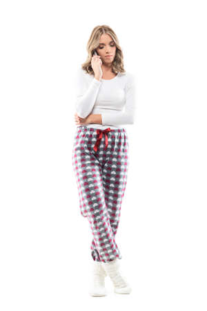 Sad concerned young beautiful woman in comfy leisure clothes talking on the phone looking down. Full body length isolated on white background. Stockfoto