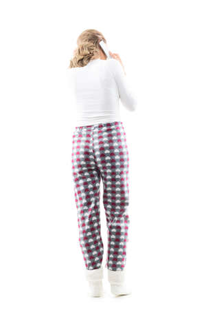 Back view of young woman in comfy pajamas talking on the cell phone looking down touching hair. Full body length isolated on white background.