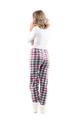 Back view of unrecognizable young woman talking on the phone standing at home in pajama. Full body length isolated on white background.