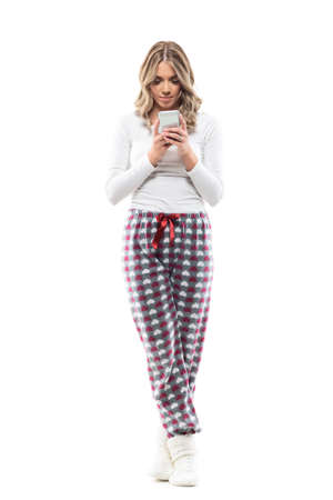 Relaxed peaceful young woman in cozy sleepwear clothes standing and using phone. Full body length isolated on white background.