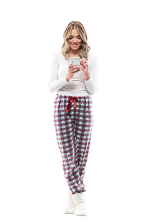Happy young woman using phone for online shopping from home wearing pajamas. Full body length isolated on white background.