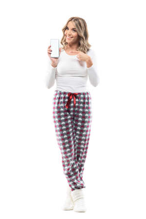 Young pretty woman in pajama advertising empty white smart phone display showing at camera. Full body length isolated on white background. Stockfoto