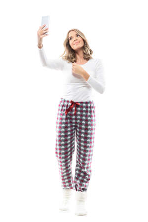 Young pretty woman in cozy home wear pajamas taking selfie with cell phone. Full body length isolated on white background. Stockfoto