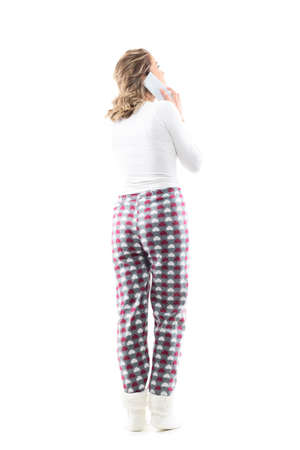 Back view of young woman in cozy pajamas talking on the phone looking up above at attention. Full body length isolated on white background.