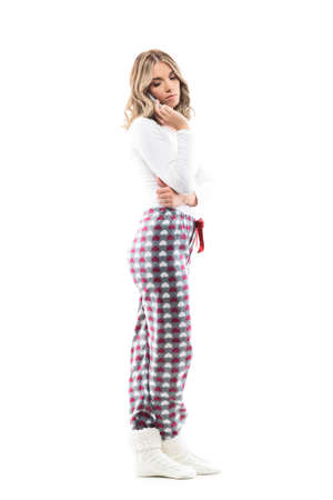 Emotional pretty young woman in pajamas talking on the cell phone looking down over shoulder. Full body length isolated on white background.