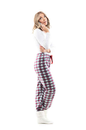 Side view of cute curious young woman in pajama talking on the phone looking back over shoulder. Full body length isolated on white background.