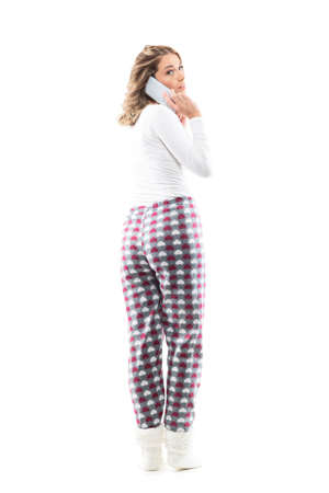 Back view of young pretty woman in pajama talking on the phone turning behind and looking at camera. Full body length isolated on white background. Stockfoto