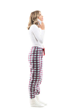 Side view of young pretty woman on the cell phone distracted watching up above interested. Full body length isolated on white background. Stockfoto
