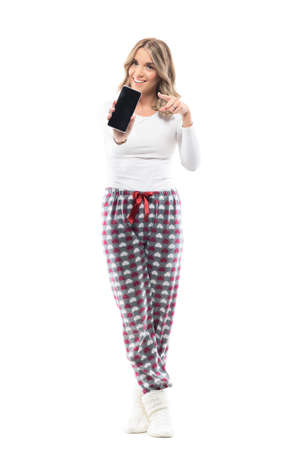 Pretty woman in pajamas holding and showing cellphone black screen pointing finger and advertising. Full body length isolated on white background.
