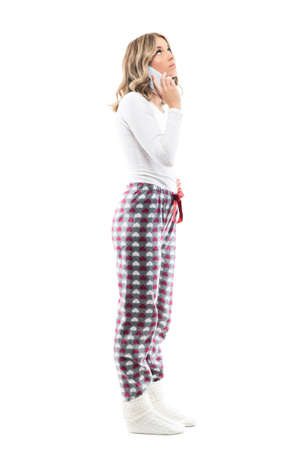 Side view of worried young woman in pajamas talking on the cell phone looking up. Full body length isolated on white background. Stockfoto