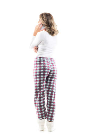 Back view of young woman in pajamas relaxing at home talking on the cell phone. Full body length isolated on white background.