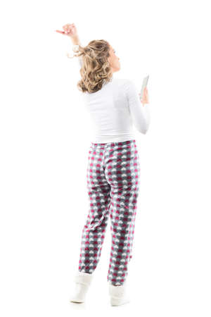 Back view of young woman in pajamas flicking and tossing hair holding cellphone. Full body length isolated on white background. Stockfoto