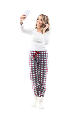Stunning beauty woman in pajamas taking selfie with smart phone touching hair. Full body length isolated on white background.