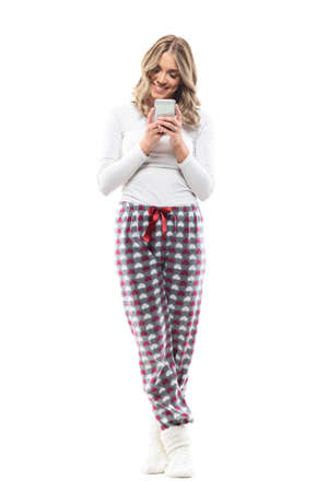 Smiling young woman using smart phone online shopping application from home in cozy clothes. Full body length isolated on white background.