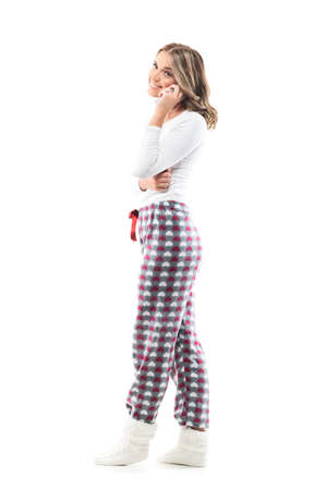 Side view of beautiful smiling young woman in pajamas talking on the cellphone looking at camera. Full body length isolated on white background. Stockfoto