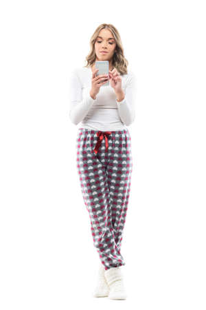 Confident serious young pretty woman using cell phone in cozy home wear. Full body length isolated on white background. Stockfoto