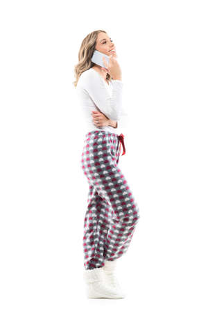 Side view of relaxed laughing joyful young pretty woman in pajamas talking on the cellphone. Full body length isolated on white background.