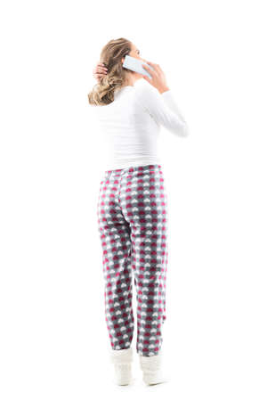 Back view of candid young woman in pajama at home talking on the phone looking up touch hair. Full body length isolated on white background.