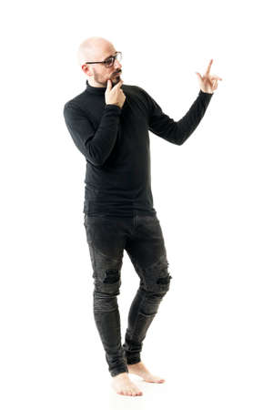 Bald barefoot offbeat style man in black clothes thinking and pointing finger at copy space. Full length portrait isolated on white background