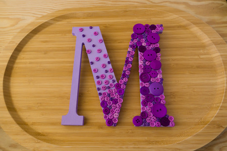 Button art letter M on wood background Banco de Imagens