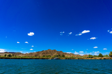 Colorado river and mountains and dredging barge under blue sky in Yuma Arizona