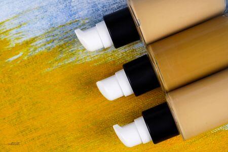 Bottle of liquid foundation on colorful background.